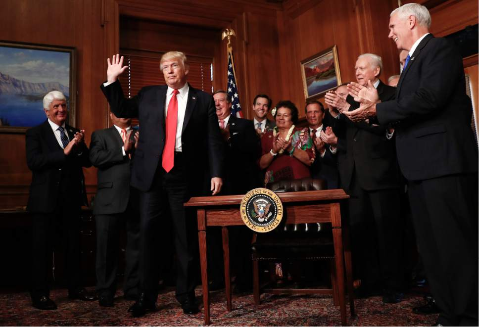 "President Donald Trump acknowledge applause after signing an Antiquities Executive Order during a ceremony at the Interior Department in Washington, Wednesday, April, 26, 2017. Th president is asking for a review of the designation of tens of millions of acres of land as ""national monuments."" Front row, from left are, Rep. Ben Bishop, R-Utah, the president and Sen. Orrin Hatch, R-Utah. (AP Photo/Carolyn Kaster)"