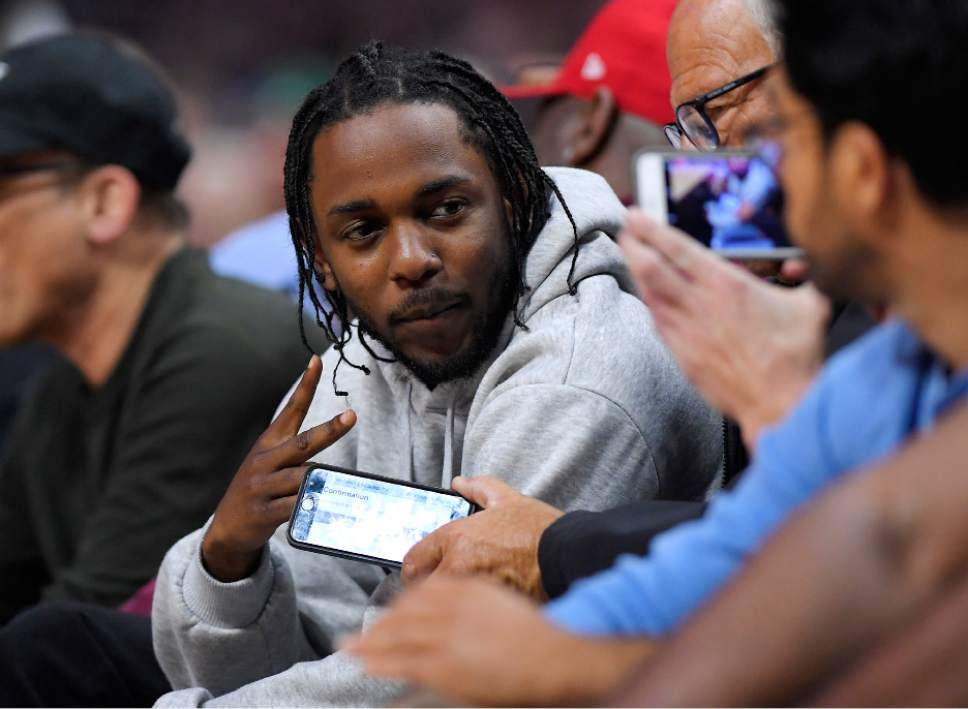 Singer Kendrick Lamar poses for a fan's picture during the first half in Game 5 of an NBA basketball first-round playoff series between the Los Angeles Clippers and the Utah Jazz, Tuesday, April 25, 2017, in Los Angeles. (AP Photo/Mark J. Terrill)