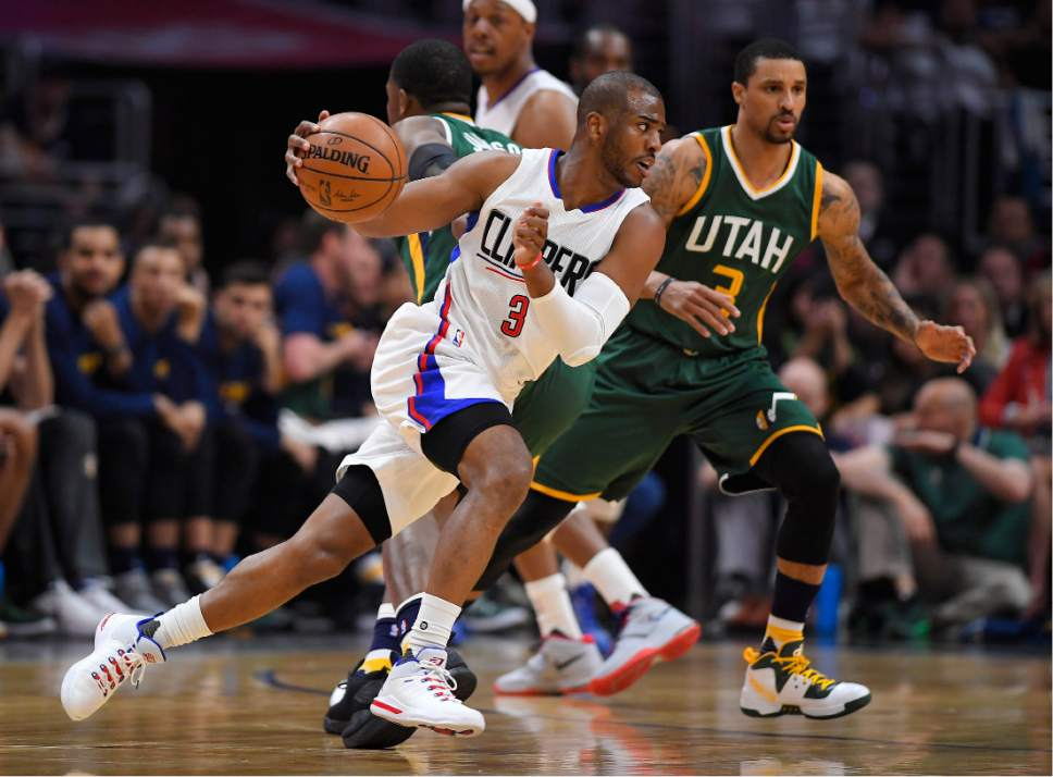 Los Angeles Clippers guard Chris Paul, left, drives past Utah Jazz guard George Hill during the first half in Game 5 of an NBA basketball first-round playoff series, Tuesday, April 25, 2017, in Los Angeles. (AP Photo/Mark J. Terrill)