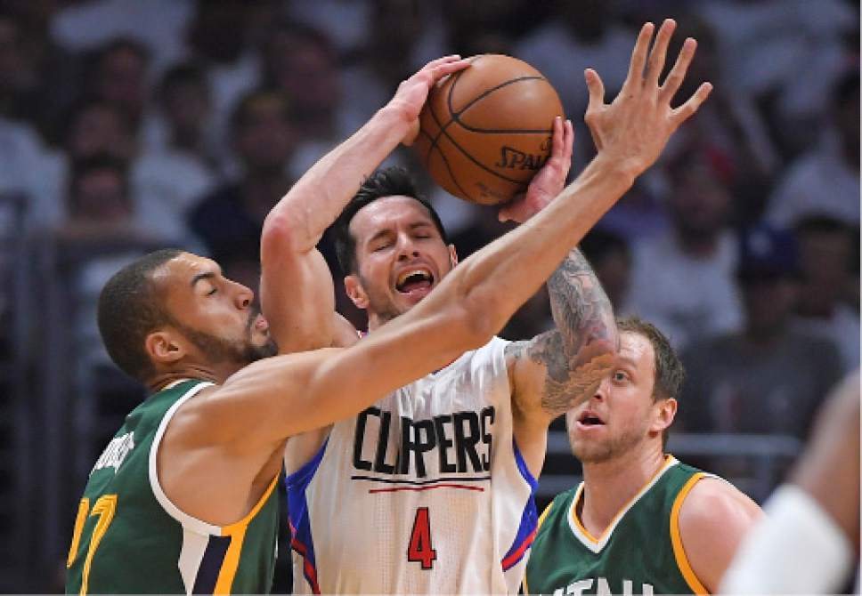 Los Angeles Clippers guard JJ Redick, center, tries to pass as Utah Jazz center Rudy Gobert, left, and forward Joe Ingles defend during the first half in Game 5 of an NBA basketball first-round playoff series, Tuesday, April 25, 2017, in Los Angeles. (AP Photo/Mark J. Terrill)