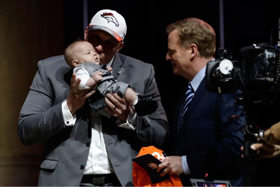 Utah's Garett Bolles, left, kisses his son, Kingston, alongside NFL commissioner Roger Goodell after being selected by the Denver Broncos during the first round of the 2017 NFL football draft, Thursday, April 27, 2017, in Philadelphia. (AP Photo/Matt Rourke)