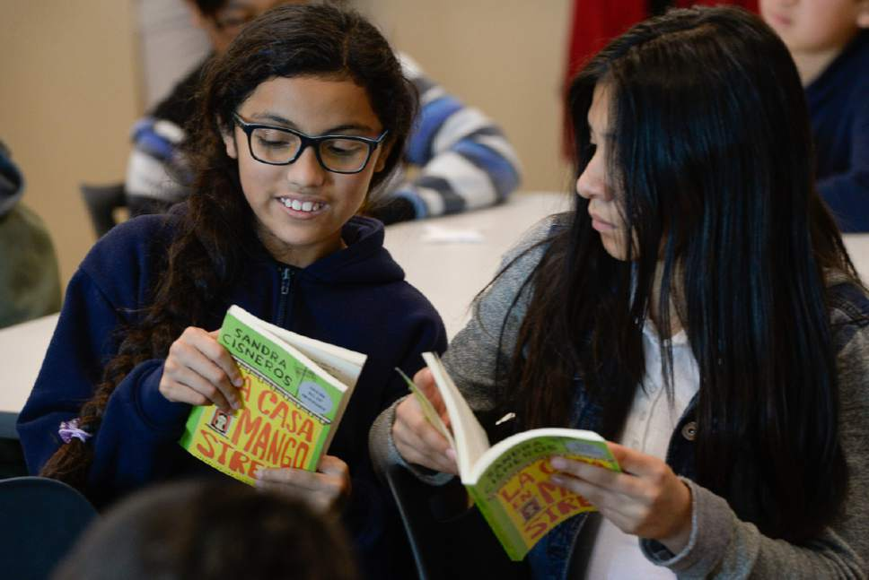 """Francisco Kjolseth   The Salt Lake Tribune Mountain View Elementary School fifth graders Merali Salgado, left, and Angie Camarillo, both 11, read from writer Sandra Cisneros book, """"The House on Mango Street,"""" as the author visited the school on Wed. April 26, 2017."""