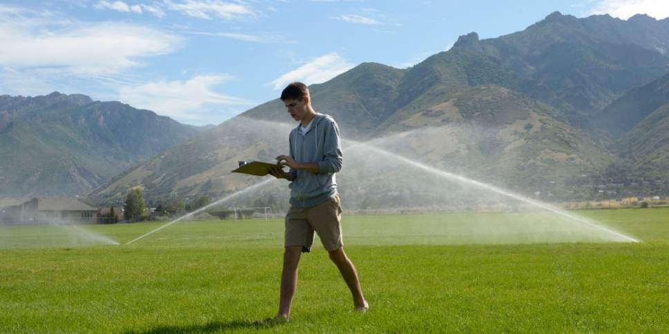Al Hartmann  |  The Salt Lake Tribune Water management intern Joseph Hawkins checks and adjusts sprinkler heads at Albion Middle School in  Sandy Tuesday July 21.  The internships are payed through the Central Utah Water Conservency District to help make watering grounds at 15 schools in the Canyons School District more efficient and the grass healthier.