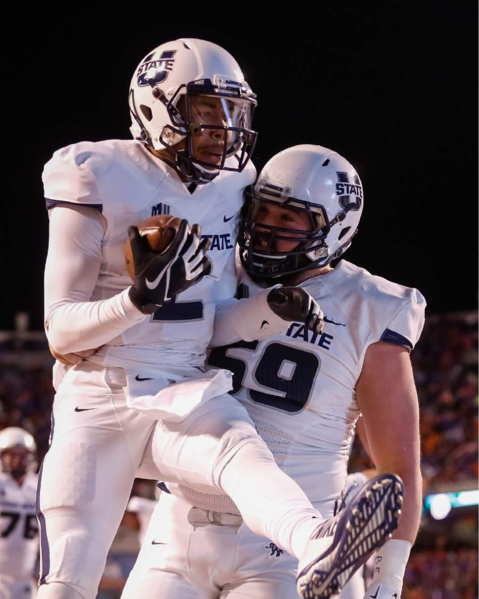 Utah State quarterback Kent Myers (2) and center Austin Stephens (59) celebrate Myers' touchdown during the first quarter of an NCAA college football game against Boise State in Boise, Idaho, on Saturday, Nov. 29, 2014. (AP Photo/Otto Kitsinger)