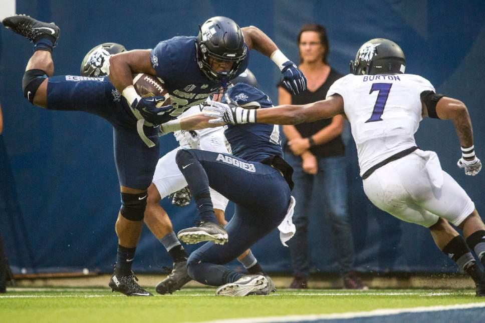 Chris Detrick  |  The Salt Lake Tribune Utah State Aggies running back Devante Mays (32) scores a touchdown past Weber State Wildcats safety Josh Burton (7) during the game at Maverik Stadium Thursday September 1, 2016.