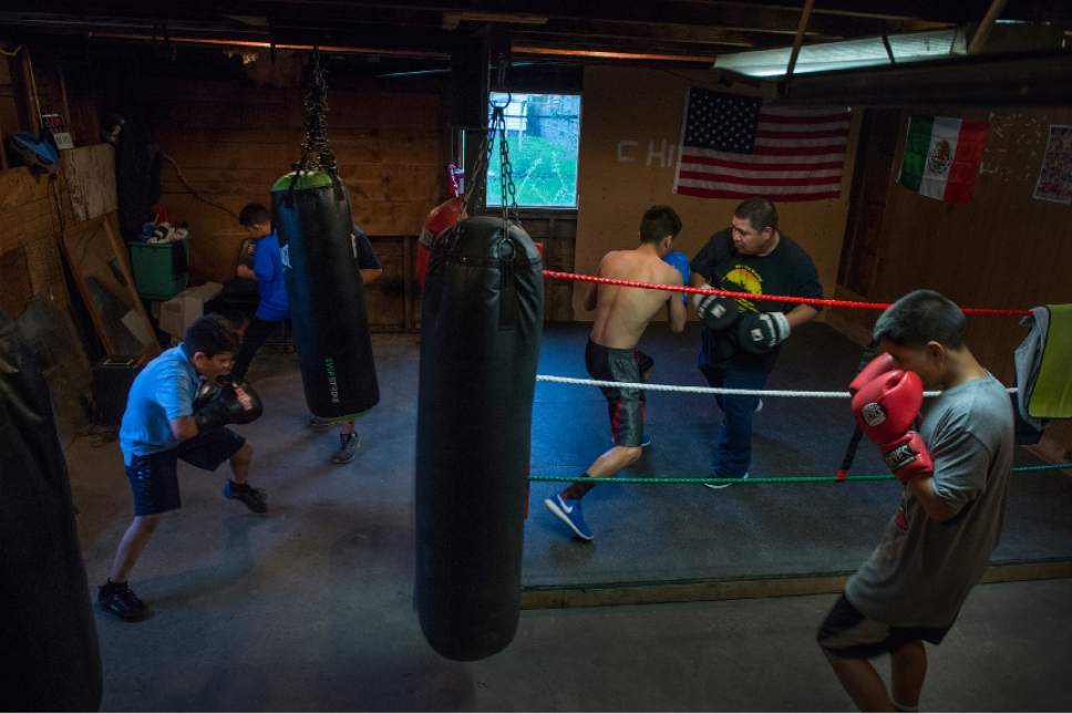 Leah Hogsten  |  The Salt Lake Tribune  Diego Alvarez, 17, of South Ogden, spars in the ring with his trainer Lalo Lopez at the tiny Los Gallitos Boxing Club gym, Tuesday, April 18, 2017. Young boxers l-r Eduardo Lopez, Jose Mata and Jayden Lopez shadow box and hit bags. Alvarez  hopes to win amateur boxing's 114-pound national title at the Golden Gloves championship for the second time this weekend in Lafayette, LA.
