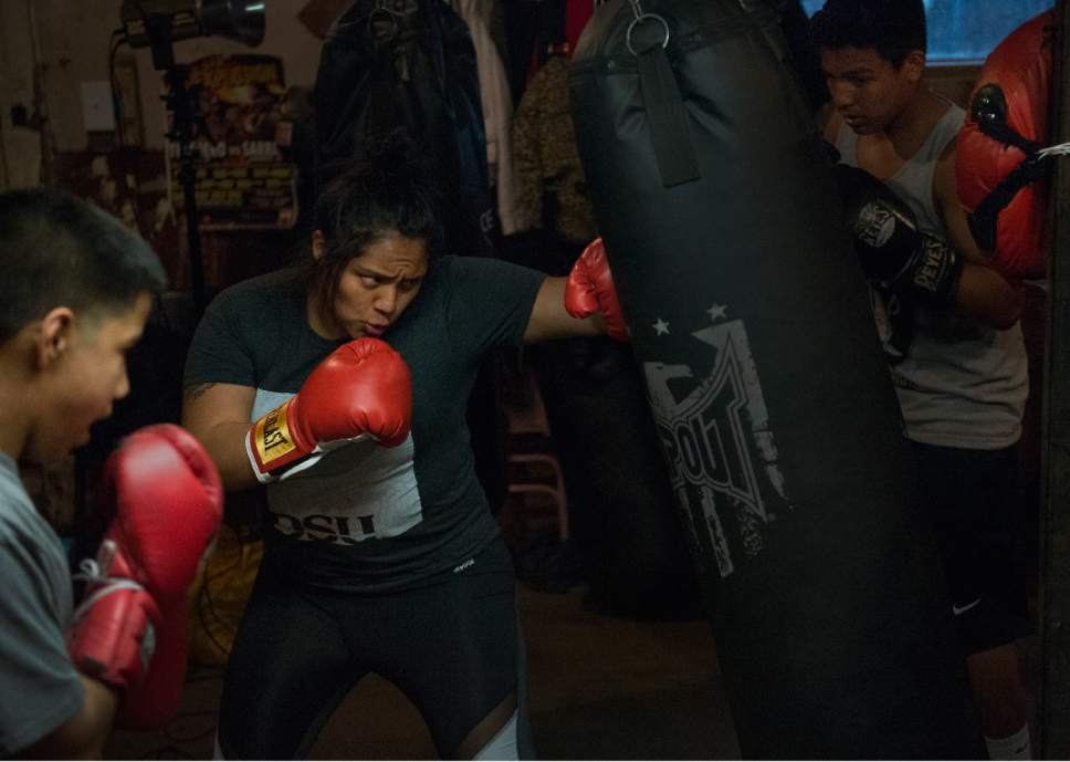 Leah Hogsten  |  The Salt Lake Tribune  l-r Jayden Lopez, Sonia Velasco and Jesse Andrade take turns punching one bag at the tiny Los Gallitos Boxing Club gym, Tuesday, April 18, 2017. The gym's champion Diego Alvarez, 17, hopes to win amateur boxing's 114-pound national title at the Golden Gloves championship for the second time this weekend in Lafayette, LA.