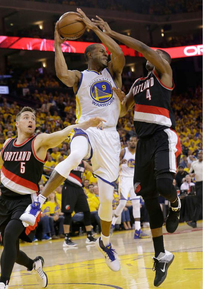 Golden State Warriors forward Andre Iguodala (9) passes the ball between Portland Trail Blazers guard Pat Connaughton (5) and forward Maurice Harkless (4) during the first half of Game 1 of a first-round NBA basketball playoff series in Oakland, Calif., Sunday, April 16, 2017. (AP Photo/Jeff Chiu)