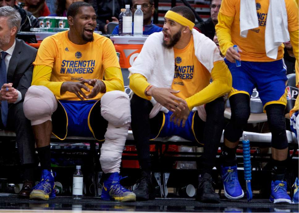 Golden State Warriors forward Kevin Durant, left, and center JaVale McGee react at the end of the game against the Portland Trail Blazers during Game 4 of an NBA basketball first-round playoff series Monday, April 24, 2017, in Portland, Ore. The Warriors won 128-103. (AP Photo/Craig Mitchelldyer)