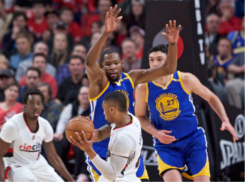 Golden State Warriors forward Kevin Durant, top, defends against Portland Trail Blazers guard Damian Lillard during the first half of Game 4 of an NBA basketball first-round playoff series, Monday, April 24, 2017, in Portland, Ore. (AP Photo/Craig Mitchelldyer)