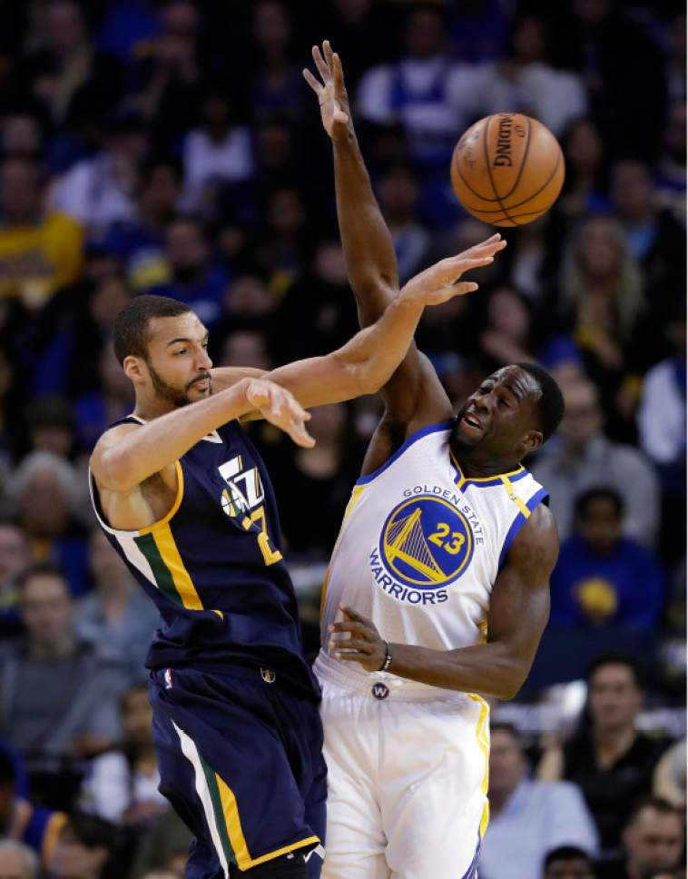 FILE - In this April 10, 2017, file photo, Utah Jazz center Rudy Gobert, left, passes as Golden State Warriors forward Draymond Green (23) defends during the first half of an NBA basketball game in Oakland, Calif. Golden State and Utah begin their best-of-seven NBA second round playoff series on Tuesday, May 2.(AP Photo/Marcio Jose Sanchez, File)