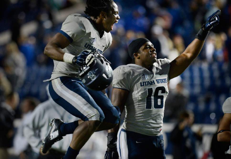 Scott Sommerdorf     The Salt Lake Tribune Utah State Aggies safety Devin Centers, left, and team mate LB Anthony Williams celebrate the win over BYU. Utah State defeated BYU 35-20 in Provo, Friday, October 1, 2014.
