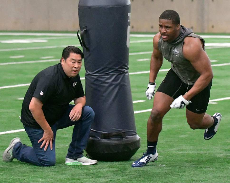 Eli Lucero     Herald Journal  Anthony Williams runs through drills as Atlanta Falcons scout Sae Woon Jo watches during USU's Pro Day on Friday March 31, 2017.