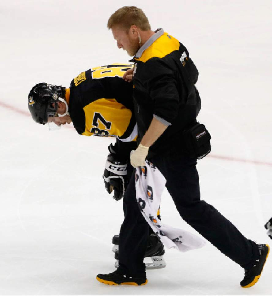 Pittsburgh Penguins  Sidney Crosby (87) is helped off the ice after being  injured b42d4dd3293d