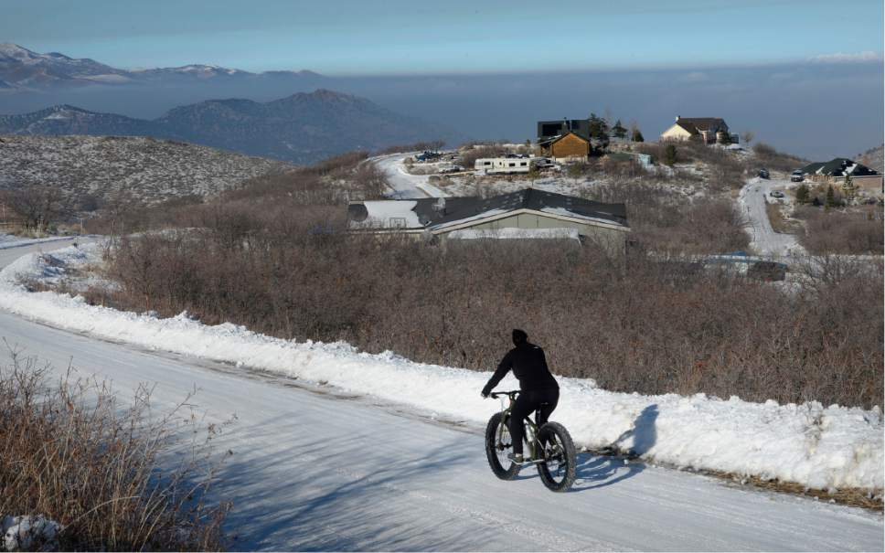 Scott Sommerdorf   |  The Salt Lake Tribune   Elena Hall heads back home after a ride above the inversion that can be seen blanketing the Salt lake Valley from Rose Canyon near Herriman, Saturday, December 31, 2016.