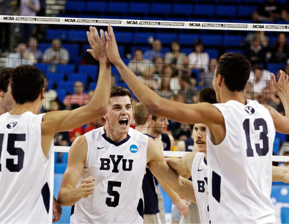 BYU's Taylor Sander (15), Russ Lavaja (5) and Ben Patch (13) celebrate a kill against Penn State in the first set of their NCAA Final Four college volleyball tournament semifinal in Los Angeles, Thursday, May 2, 2013. (AP Photo/Reed Saxon)