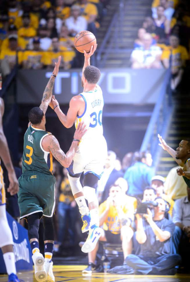 Steve Griffin  |  The Salt Lake Tribune   Golden State Warriors guard Stephen Curry (30) shoots over Utah Jazz guard George Hill (3) as a strobe light illuminates him during NBA playoff game between the Utah Jazz and the Golden State Warriors at Oracle Arena in Oakland Tuesday May 2, 2017.