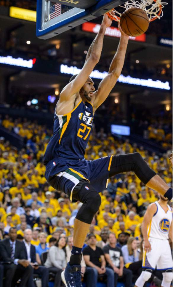 Steve Griffin  |  The Salt Lake Tribune   Utah Jazz center Rudy Gobert (27) hangs on the rim after slamming the ball during game 2 of the NBA playoff game between the Utah Jazz and the Golden State Warriors at Oracle Arena in Oakland Thursday May 4, 2017.