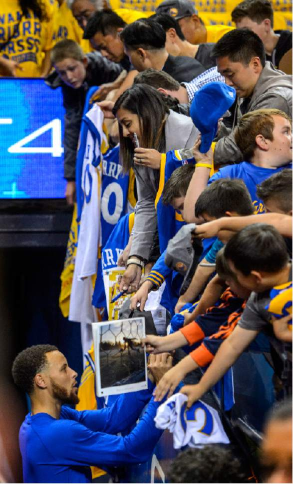Steve Griffin  |  The Salt Lake Tribune   Fans hang over the railing as Golden State Warriors guard Stephen Curry (30) signs autographs before game 2 of the NBA playoff game between the Utah Jazz and the Golden State Warriors at Oracle Arena in Oakland Thursday May 4, 2017.