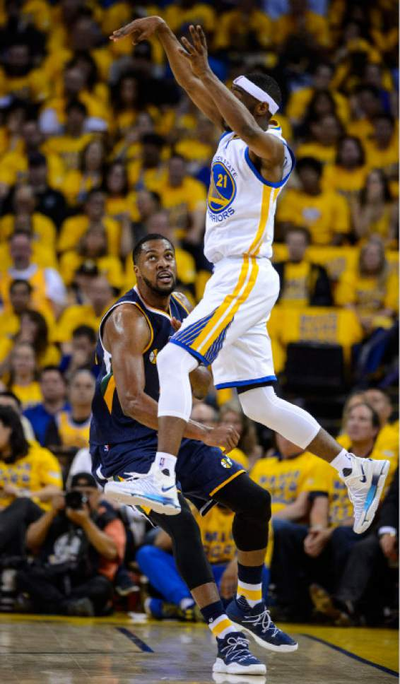 Steve Griffin  |  The Salt Lake Tribune   Golden State Warriors guard Ian Clark (21) leaps in the air as he passes over Utah Jazz forward Derrick Favors (15) during game 2 of the NBA playoff game between the Utah Jazz and the Golden State Warriors at Oracle Arena in Oakland Thursday May 4, 2017.