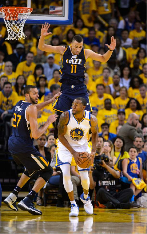 Steve Griffin  |  The Salt Lake Tribune   Utah Jazz guard Dante Exum (11) leaps above Golden State Warriors forward Andre Iguodala (9) as he cuts him off during game 2 of the NBA playoff game between the Utah Jazz and the Golden State Warriors at Oracle Arena in Oakland Thursday May 4, 2017.