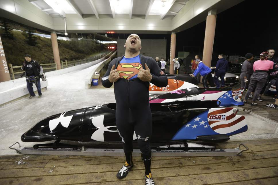 Steve Holcomb displays his Superman shirt as he poses for a photograph in front of his sled after the United States four-man bobsled team trials  on Saturday, Oct. 26, 2013, in Park City, Utah. Holcomb and his crew came in first place. (AP Photo/Rick Bowmer)