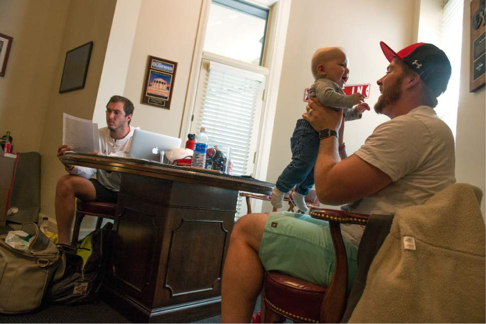 Leah Hogsten  |  The Salt Lake Tribune  University of Utah kicker Andy Phillips (right), holding son Gus, 7 mos., talks with University of Utah long snapper Chase Dominguez (left) in Phillips' fathers office, Greg Phillips, who is also both their sports agent on Saturday. Phillips and Dominguez negotiated NFL contracts, April 29, 2017 as undrafted free agents. Phillips signed with the Chicago Bears and Dominguez signed with the New Orleans Saints.