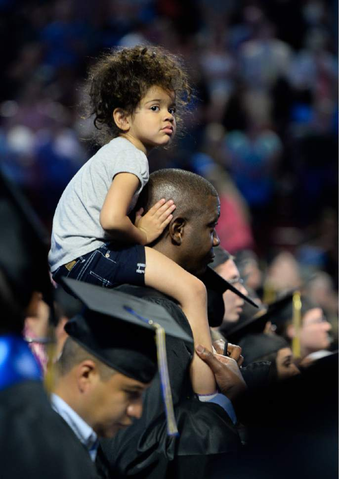 Francisco Kjolseth   The Salt Lake Tribune Mackell Gilot, 3, perches on top of her father Mackenton's shoulders during the start of commencement ceremonies for Salt Lake Community College at the Maverik Center on Friday, May 5, 2017.