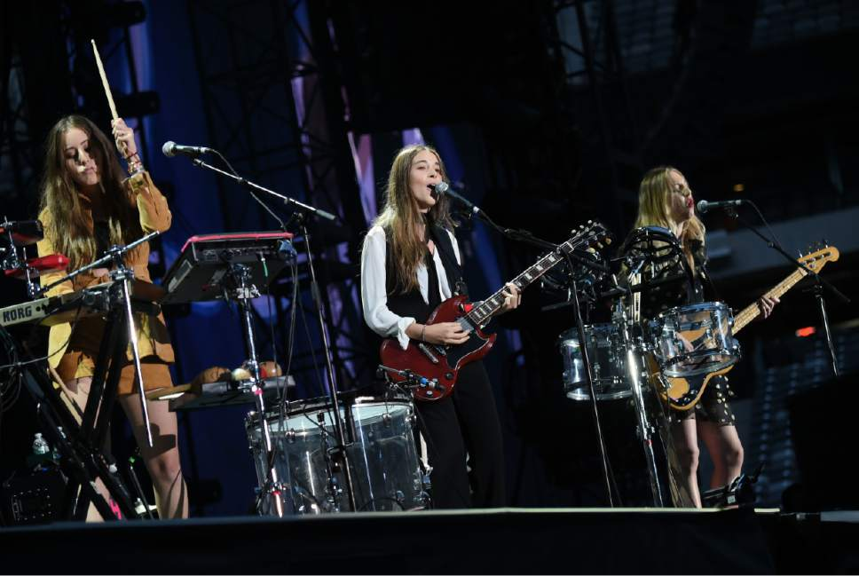 "Alana Haim, left, Danielle Haim, and Este Haim, right, of the group Haim perform during Taylor Swift's ""1989"" tour at MetLife Stadium in East Rutherford on Friday, July 10, 2015, in New Jersey. (Photo by Evan Agostini/Invision/AP)"