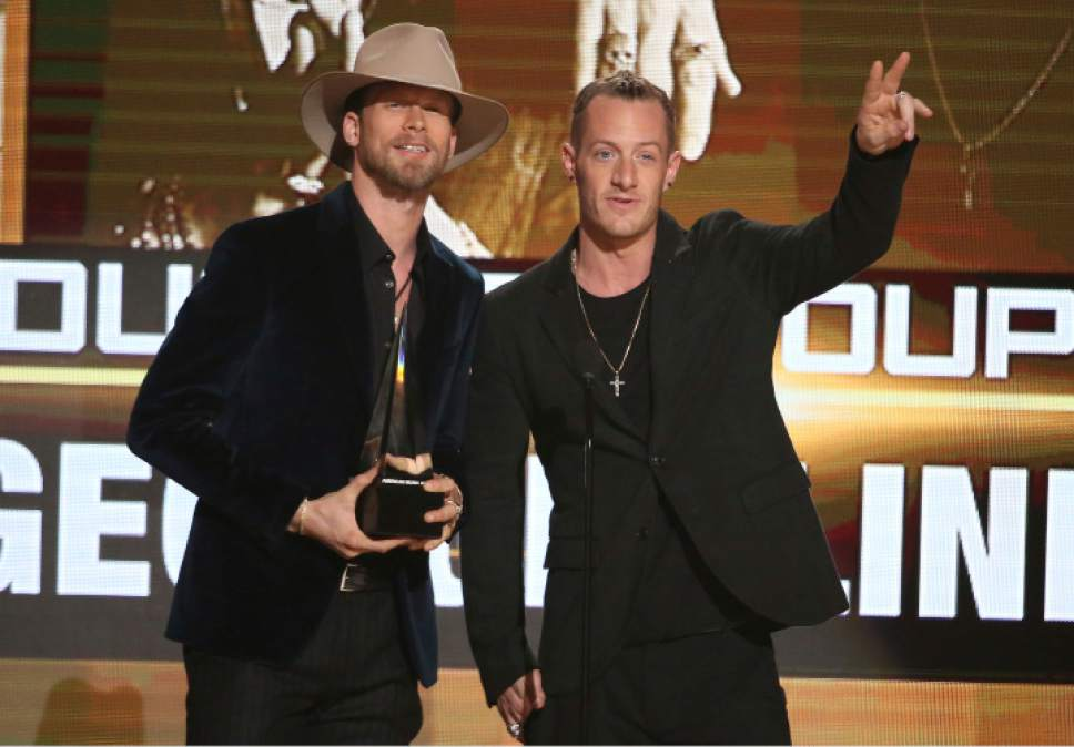 Brian Kelley, left, and Tyler Hubbard, of Florida Georgia Line, accept the award for favorite country duo/group at the American Music Awards at the Microsoft Theater on Sunday, Nov. 20, 2016, in Los Angeles. (Photo by Matt Sayles/Invision/AP)