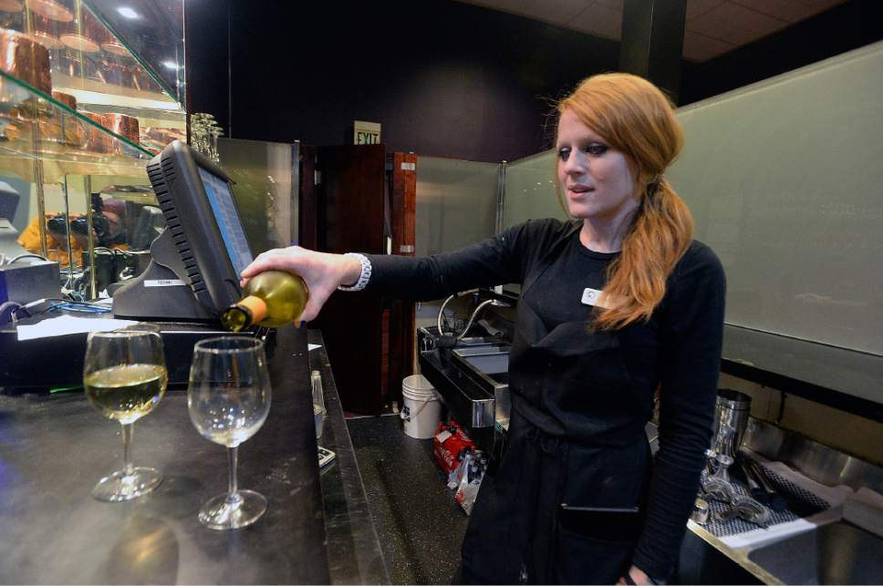 """Al Hartmann      Tribune file photo Server Kerry Harding pours glasses of white wine for customers behind the """"Zion Curtain"""" at Lamb's Grill in Salt Lake City Wednesday Jan. 11. A new state law will allow restaurants to use alternatives to the 7-foot barrier to block the view of alcohol-dispensing areas from minor patrons."""
