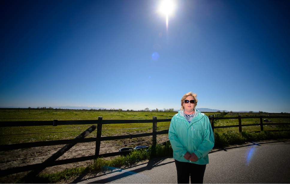 Trent Nelson  |  The Salt Lake Tribune Christine Mikkelsen in the quiet open space behind her Farmington home that may soon be occupied by the West Davis Corridor highway, Thursday May 4, 2017. Mikkelsen and her husband moved into their home six years ago when they were told they would never lose their view thanks to the Buffalo Ranch that would prevent development from blocking the sweeping vista of the Great Salt Lake and Antelope Island. Later, when they learned about the West Davis Corridor, a roughly 20-mile stretch of new freeway planned in northern Utah, with a $600 million-plus price tag, Mikkelsen became heavily involved in the Save Farmington group that has opposed the project. ìMost people who bought out here bought for the view, for the quiet and for the country feel,î Mikkelsen says. Now they will live with the noise and air pollution and a close up view of a freeway in their backyards and she says all state taxpayers will live with the bill of a very costly project.