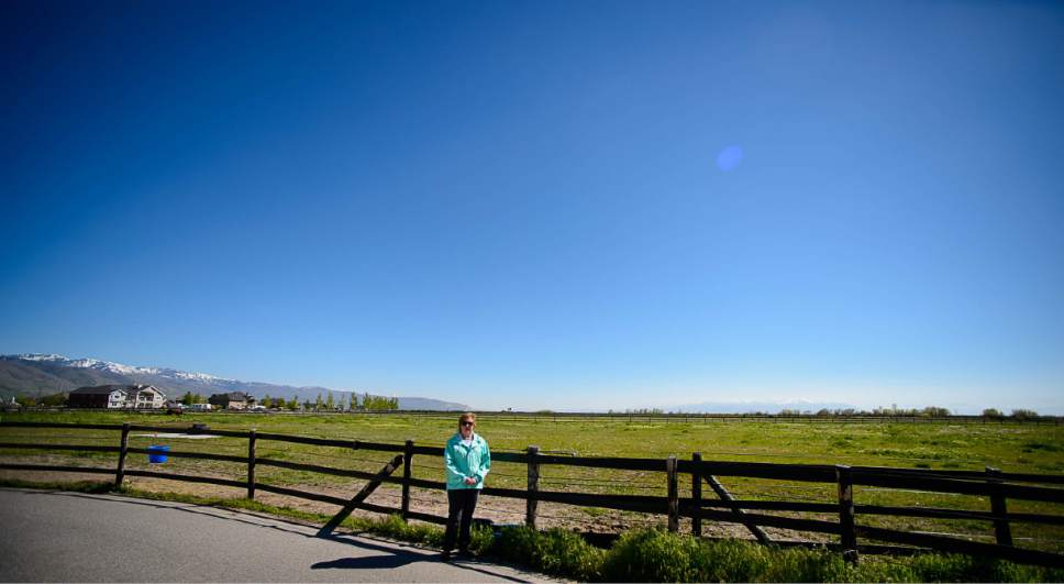 "Trent Nelson  |  The Salt Lake Tribune Christine Mikkelsen in the quiet open space behind her Farmington home that may soon be occupied by the West Davis Corridor highway, Thursday May 4, 2017. Mikkelsen and her husband moved into their home six years ago when they were told they would never lose their view thanks to the Buffalo Ranch that would prevent development from blocking the sweeping vista of the Great Salt Lake and Antelope Island. Later, when they learned about the West Davis Corridor, a roughly 20-mile stretch of new freeway planned in northern Utah, with a $600 million-plus price tag, Mikkelsen became heavily involved in the Save Farmington group that has opposed the project. ""Most people who bought out here bought for the view, for the quiet and for the country feel,"" Mikkelsen says. Now they will live with the noise and air pollution and a close up view of a freeway in their backyards and she says all state taxpayers will live with the bill of a very costly project."