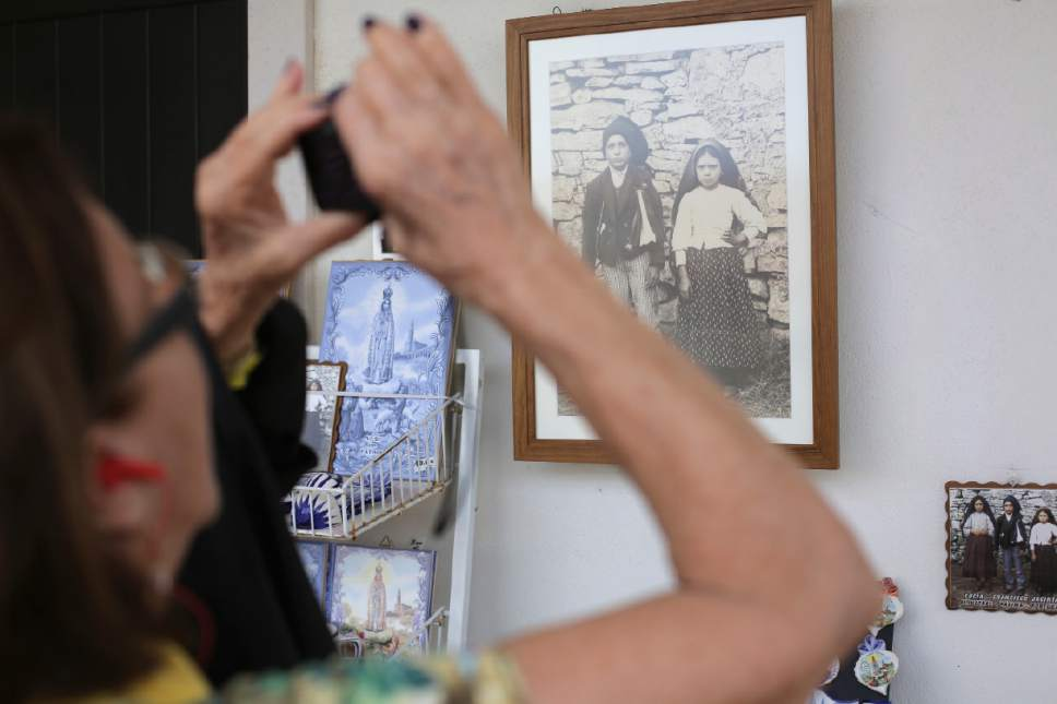 In this photo taken May 4 2017, a shop selling souvenirs displays a photo of Francisco and Jacinta Marto near the house where they lived in the village of Aljustrel, outside Fatima, Portugal. Pope Francis is visiting the Fatima shrine on May 12 and 13 to canonize Francisco and Jacinta Marto, two Portuguese shepherd children who say they saw visions of the Virgin Mary 100 years ago. (AP Photo/Armando Franca)
