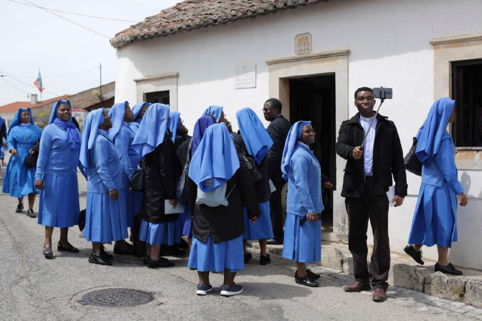 In this photo taken May 4 2017, a priest takes a selfie with a group of nuns before visiting the house where Francisco and Jacinta Marto lived in the village of Aljustrel, outside Fatima, Portugal. Pope Francis is visiting the Fatima shrine on May 12 and 13 to canonize Francisco and Jacinta Marto, two Portuguese shepherd children who say they saw visions of the Virgin Mary 100 years ago. (AP Photo/Armando Franca)