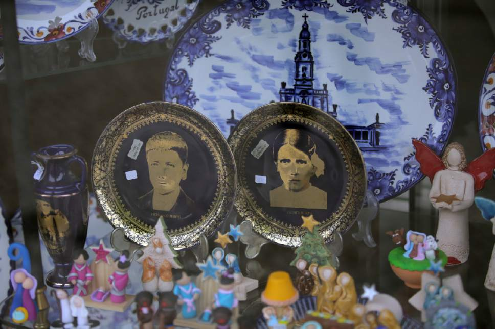 In this photo taken May 4, 2017, china plates with images of Francisco and Jacinta Marto are displayed for sale in a shop window in Fatima, Portugal. Pope Francis is visiting the Fatima shrine on May 12 and 13 to canonize Francisco and Jacinta Marto, two Portuguese shepherd children who say they saw visions of the Virgin Mary 100 years ago. (AP Photo/Armando Franca)