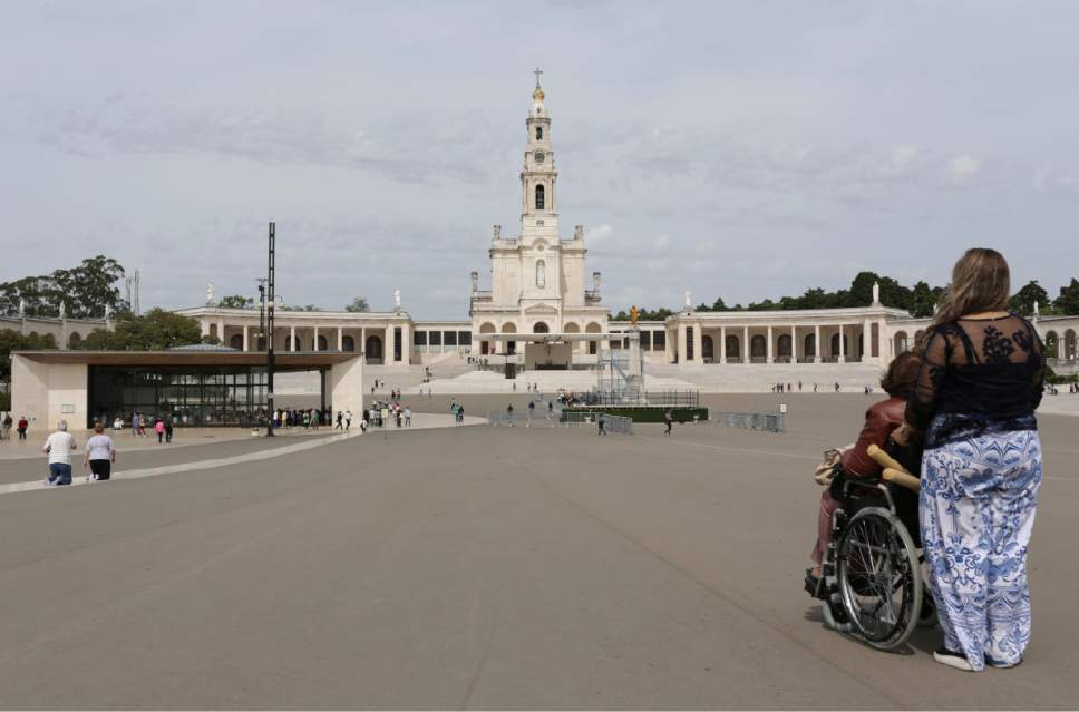 In this photo taken May 4, 2017, two women pause in front of the Fatima Basilica, center, and the Chapel of the Apparitions, at left, at the Fatima Sanctuary in Fatima, Portugal. Pope Francis is expected to pray at the chapel when he visits the Fatima shrine on May 12 and 13 to canonize two Portuguese shepherd children who say they saw visions of the Virgin Mary 100 years ago. (AP Photo/Armando Franca)