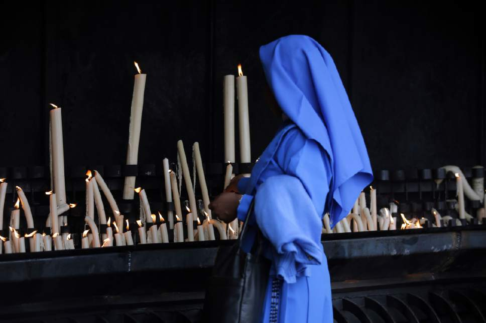In this photo taken May 4, 2017, a nun lights a candle at the Fatima Sanctuary in Fatima, Portugal. Pope Francis is visiting the Fatima shrine on May 12 and 13 to canonize two Portuguese shepherd children who say they saw visions of the Virgin Mary 100 years ago. (AP Photo/Armando Franca)