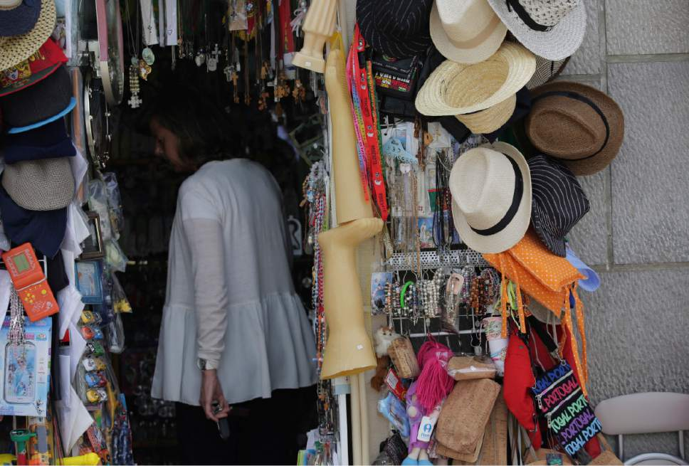 In this photo taken May 4, 2017, items hang for sale outside a shop in Fatima, Portugal. The wax figures are bought by pilgrims to be offered to the Virgin in retribution for some blessing. Pope Francis is visiting the Fatima shrine on May 12 and 13 to canonize two Portuguese shepherd children who say they saw visions of the Virgin Mary 100 years ago. (AP Photo/Armando Franca)