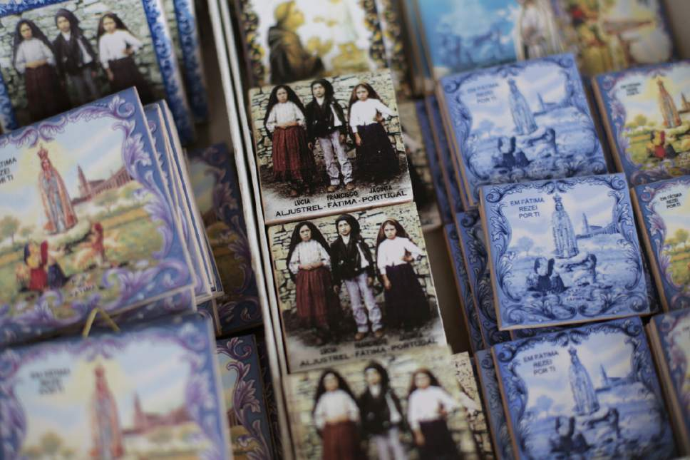 In this photo taken May 4, 2017, souvenir tiles are displayed for sale at a shop in the village of Aljustrel, outside Fatima, Portugal. The tiles show Lucia Santos, Francisco Marto and Jacinta Marto, the Portuguese shepherd children who say they saw visions of the Virgin Mary 100 years ago. Pope Francis is visiting the Fatima shrine on May 12 and 13 to canonize Francisco and Jacinta Marto. (AP Photo/Armando Franca)