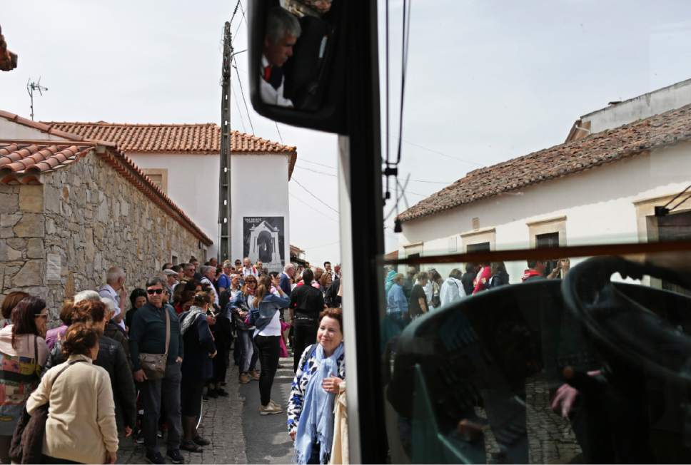 In this photo taken May 4, 2017, a bus driver negotiates his way among pilgrims waiting to visit the house where Francisco and Jacinta Marto lived, at right, in the village of Aljustrel, outside Fatima, Portugal. Pope Francis is visiting the Fatima shrine on May 12 and 13 to canonize Francisco and Jacinta Marto, two Portuguese shepherd children who say they saw visions of the Virgin Mary 100 years ago. (AP Photo/Armando Franca)