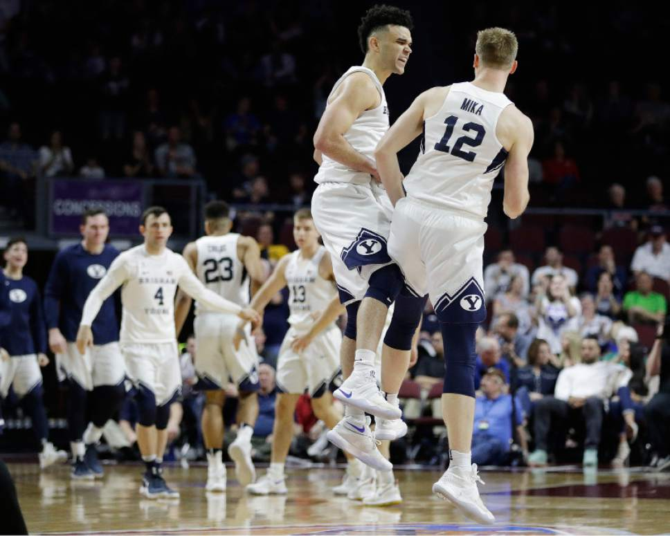 BYU's Elijah Bryant, left, and Eric Mika celebrate after a play against Loyola Marymount during the first half of a West Coast Conference tournament NCAA college basketball game Saturday, March 4, 2017, in Las Vegas. (AP Photo/John Locher)