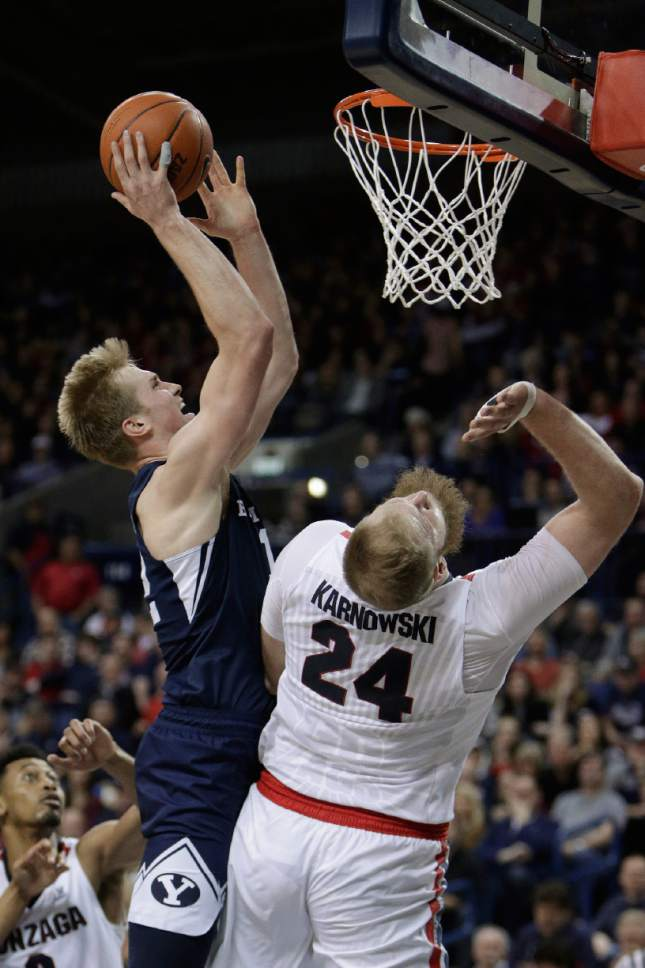 BYU forward Eric Mika, left, is fouled by Gonzaga center Przemek Karnowski (24) while shooting during the second half of an NCAA college basketball game in Spokane, Wash., Saturday, Feb. 25, 2017. BYU won 79-71. (AP Photo/Young Kwak)