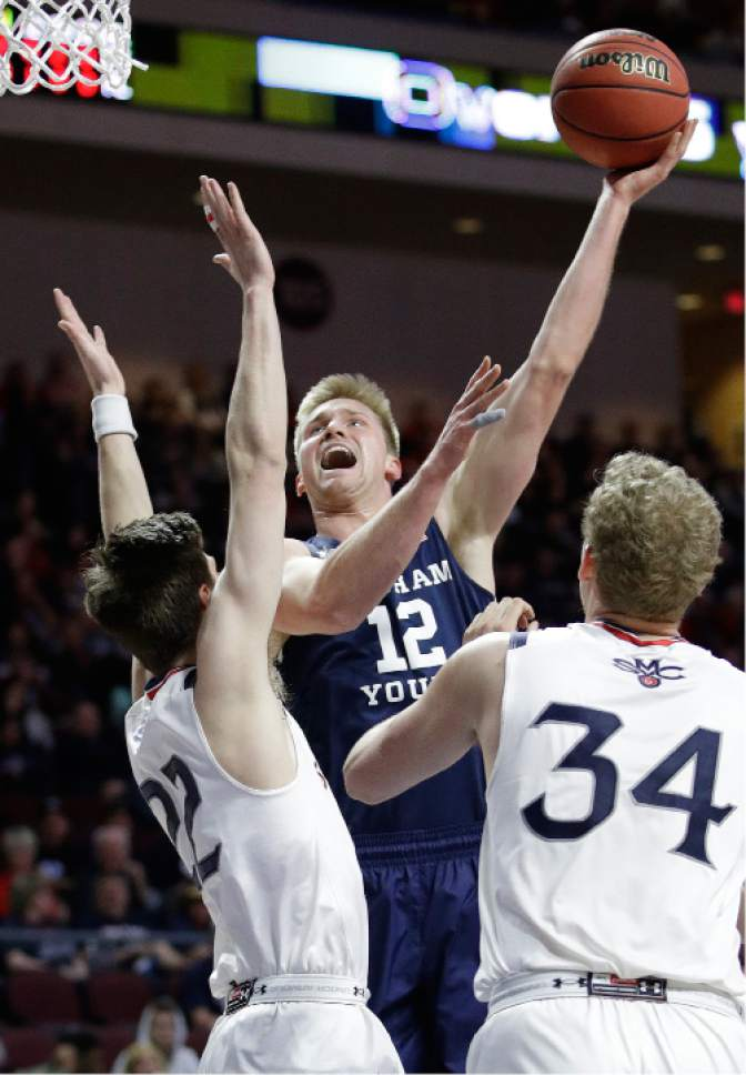 BYU's Eric Mika (12) shoots against Saint Mary's Dane Pineau, left, and Jock Landale during the first half of a West Coast Conference tournament NCAA college basketball game Monday, March 6, 2017, in Las Vegas. (AP Photo/John Locher)
