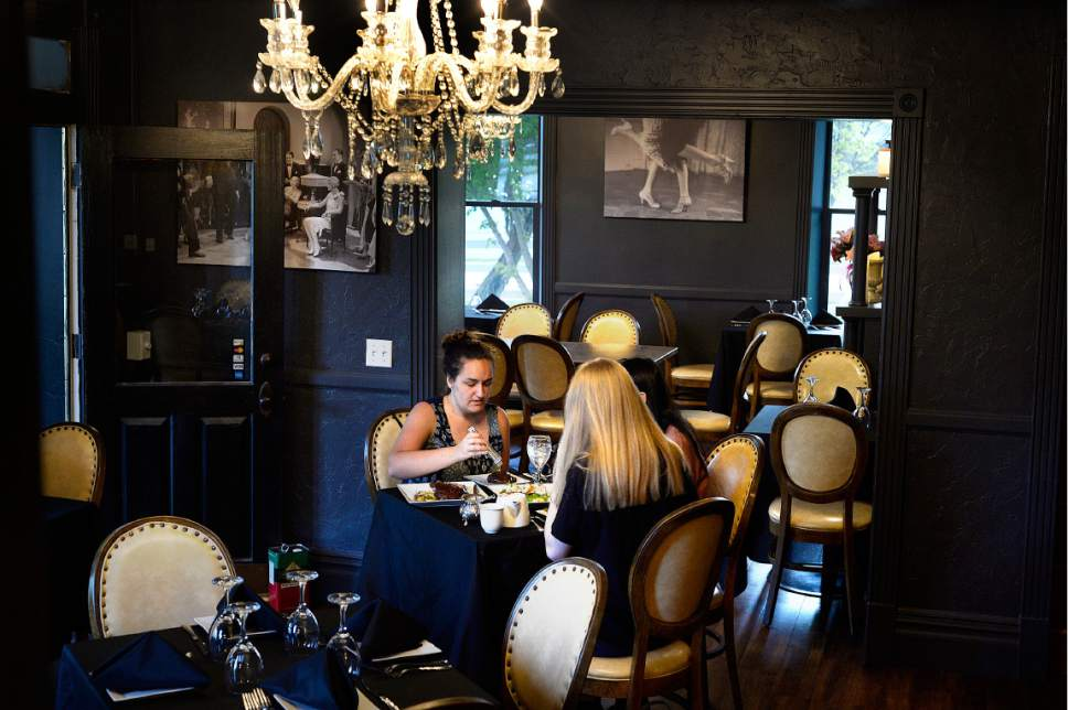 Scott Sommerdorf | The Salt Lake Tribune The 1920s speakeasy feel of the Charleston Cafe in Draper is accentuated by dark painted interiors with period photos. Located in an historic home, built in 1878, the restaurant has a vintage, 1920s feel, Friday, May 5, 2017.