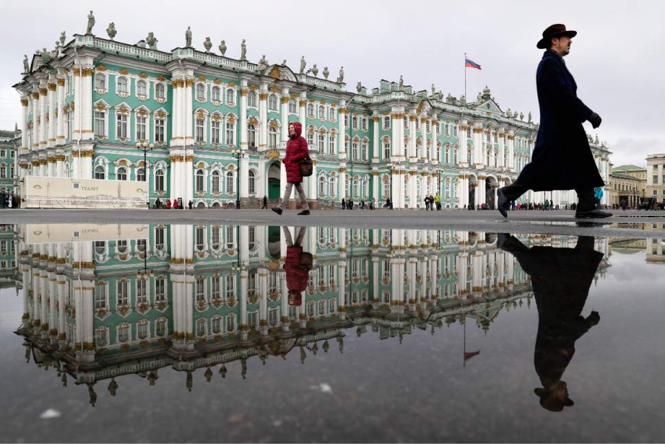 In this Saturday, March 11, 2017 photo people walk along the Zimny (Winter) Palace at Dvortsovaya Square in St. Petersburg, Russia. A century after the days that shook the world, the anniversary of the 1917 revolution in Russia is being marked with little official fanfare from the Kremlin. It once was celebrated with pomp and parades but now no longer fits the narrative of political and religious leaders. (AP Photo/Dmitri Lovetsky)