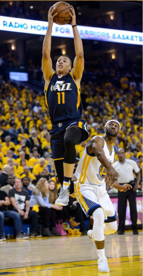 Steve Griffin  |  The Salt Lake Tribune   Utah Jazz guard Dante Exum (11) gets past Golden State Warriors guard Ian Clark (21) as he gets to the basket during game 2 of the NBA playoff game between the Utah Jazz and the Golden State Warriors at Oracle Arena in Oakland Thursday May 4, 2017.