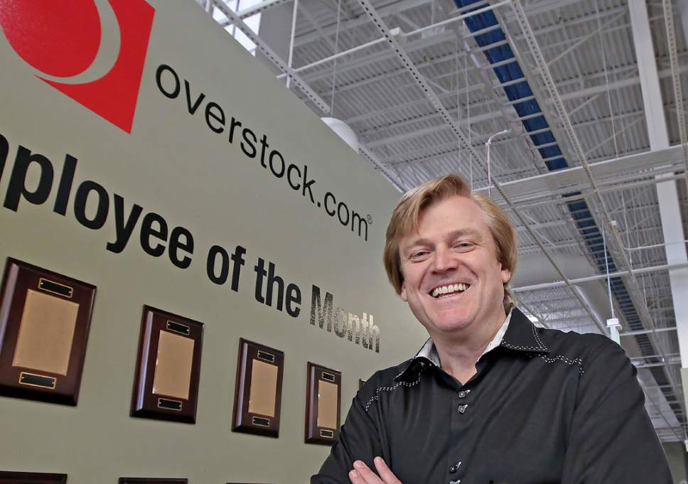FILE - This March 25, 2010 file photo, Chairman and CEO of OverStock.com Patrick Byrne poses for a picture by the employee of the month wall at the warehouse of Overstock.com outside of Salt Lake City, Utah. Emboldened by the new White House administration, advocates including Byrne, the money man behind Utah's ambitious voucher proposal that was crushed by voters a decade ago, say there is a renewed appetite to expand school choice in the state. (AP Photo/George Frey, file)