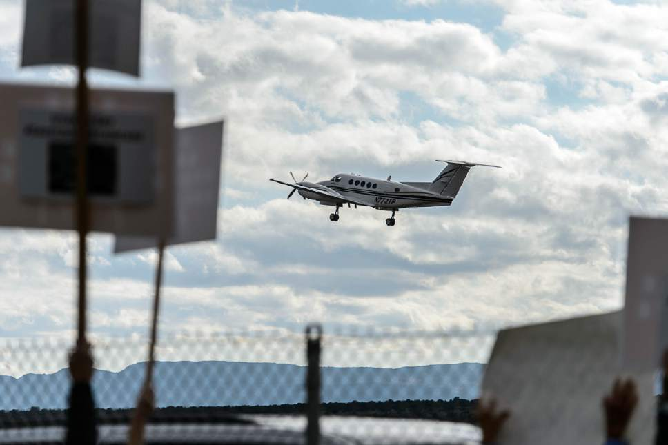 Trent Nelson  |  The Salt Lake Tribune Protest signs frame a plane taking off from Kanab Airport following a news conference with Secretary of the Interior Ryan Zinke, Wednesday May 10, 2017.