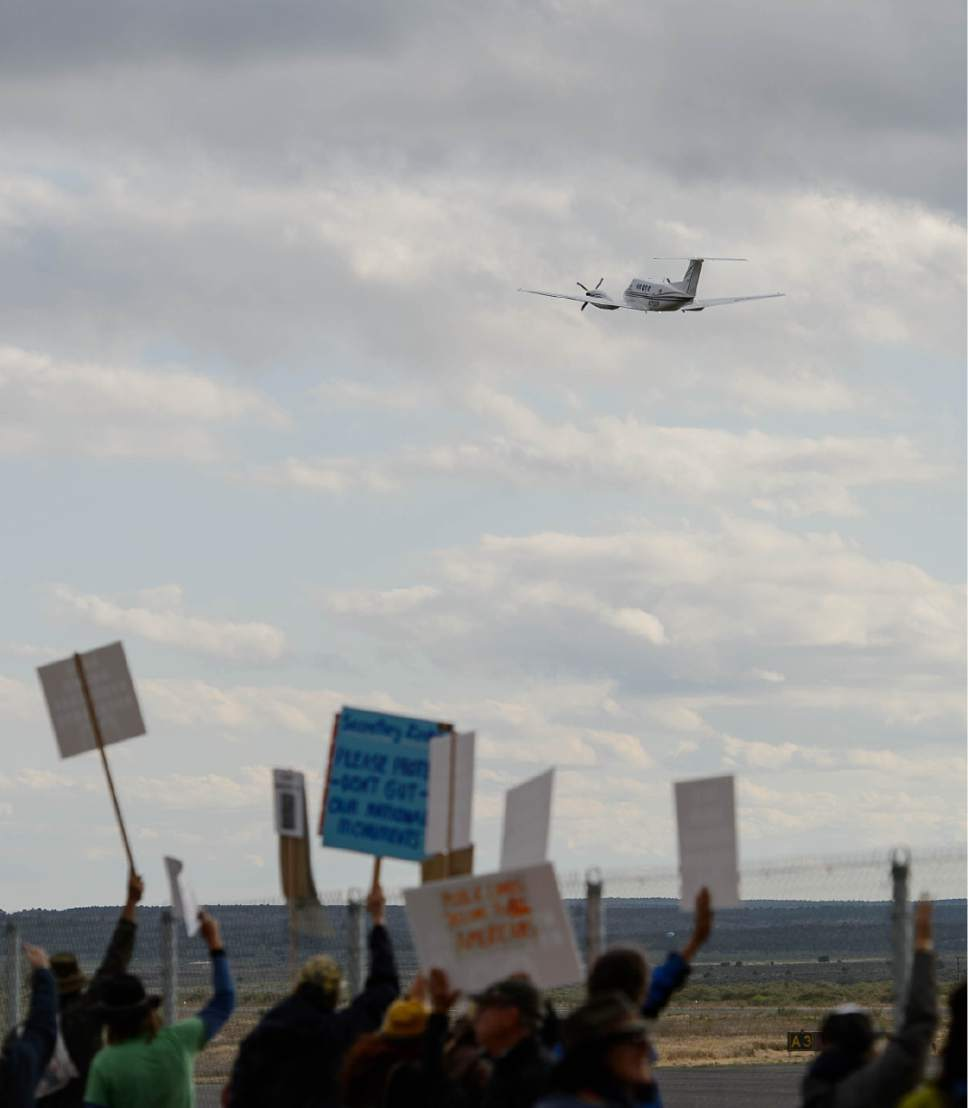 Trent Nelson  |  The Salt Lake Tribune Protest are held aloft as a plane takes off from Kanab Airport following a news conference with Secretary of the Interior Ryan Zinke, Wednesday May 10, 2017.